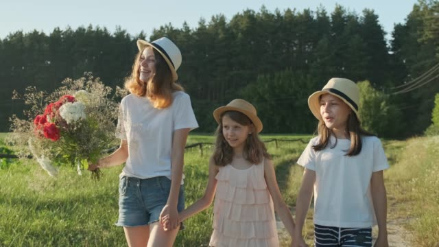 Children are three girls with bouquet of flowers holding hands walking along a country road