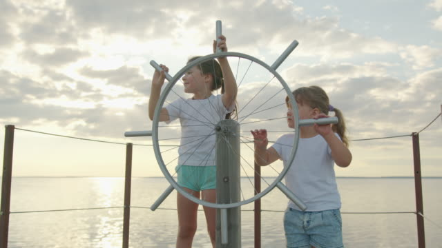 Children at the helm of the ship. Happy childhood.
