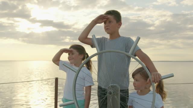 children at the helm of the ship. happy childhood. - ster fragment pojazdu filmów i materiałów b-roll