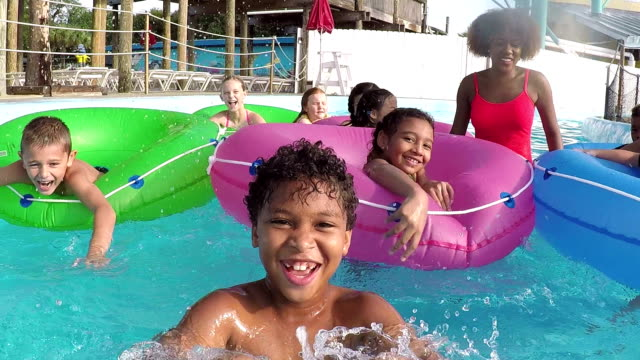 Children at water park on lazy river with camp counselors video