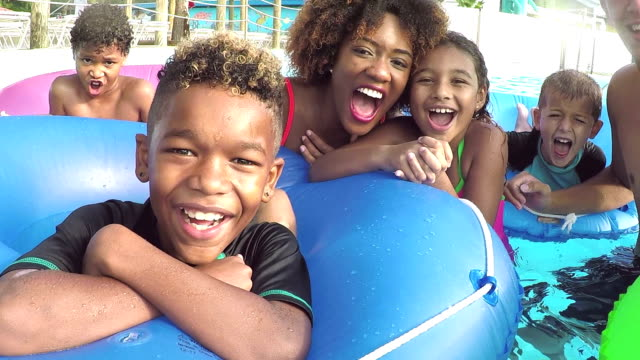 Children at water park on lazy river with camp counselors A multi-ethnic group of children at a water park with two camp counselors on inflatable rings float down the lazy river. pool party stock videos & royalty-free footage