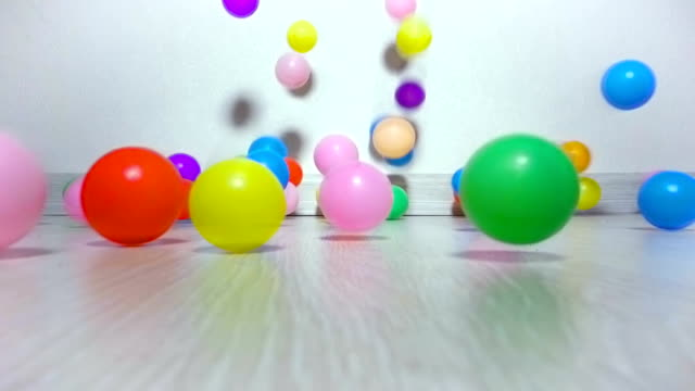 children balls slowly fall on floor - giocattolo video stock e b–roll