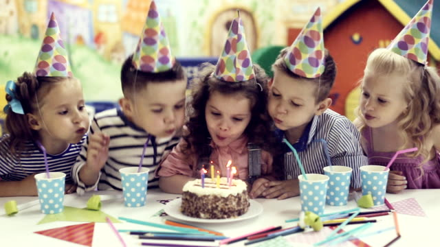 children blowing out candles on birthday cake video