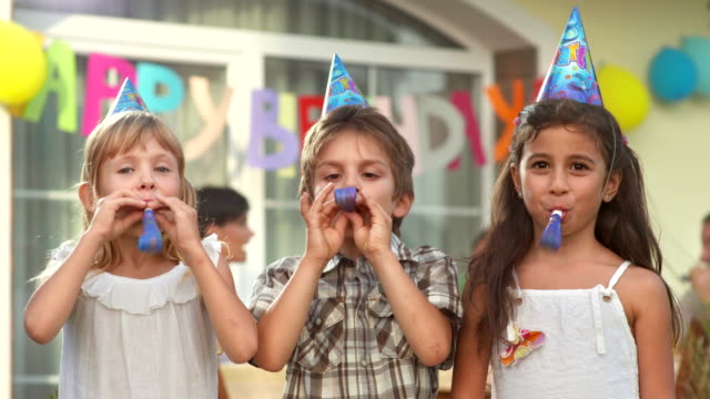 HD: Children Blowing Party Horn Blowers HD1080p: CLOSE UP portrait of three children blowing party horn blowers while having fun at birthday party. happy birthday stock videos & royalty-free footage
