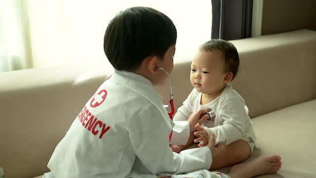 barn pojke spelar läkare med sin baby i lekrummet eller dagis. - föreställningsförmåga bildbanksvideor och videomaterial från bakom kulisserna