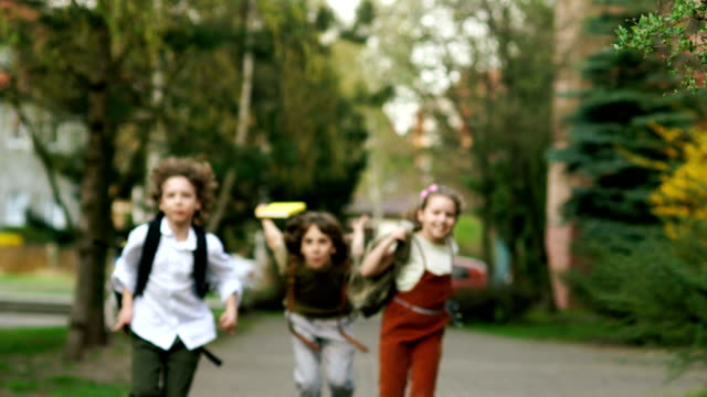 Children, boys and girls run from school, waving backpacks. Fun holidays. Back to school. Children Day video