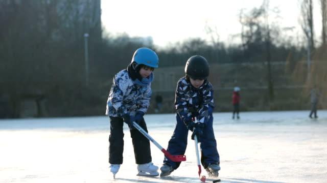 vidéos et rushes de enfants, garçons, amis et frères, jouer au hockey et le patinage dans le parc sur le lac gelé, hiver sur coucher de soleil - hockey sur glace