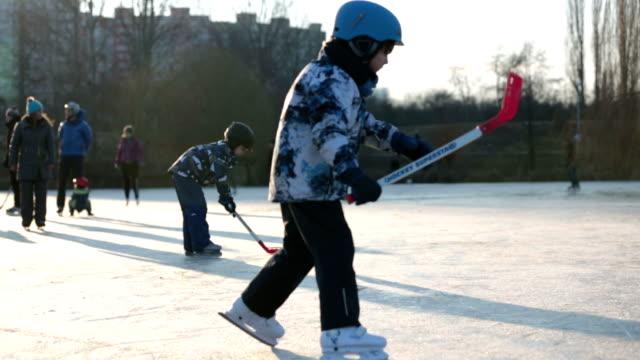 子供、男の子、友人や兄弟は、日没の冬の凍結湖の公園でホッケーやスケートをプレイ - チェコ共和国点の映像素材/bロール