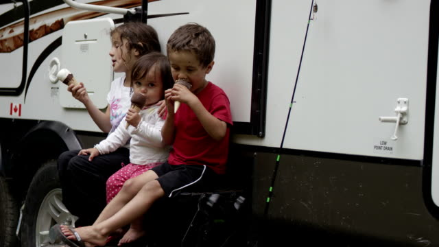 Children camping and eating ice cream video