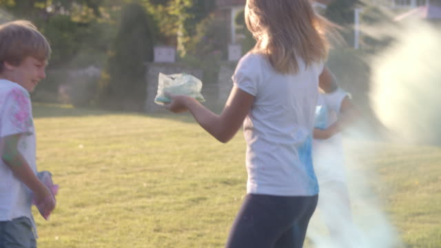 vídeos de stock e filmes b-roll de children celebrating holi festival with paint party - holi