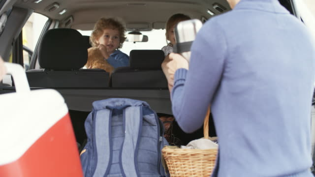 子供のピクニックのための車のパッキングの両親とチャット - 荷造り点の映像素材/bロール