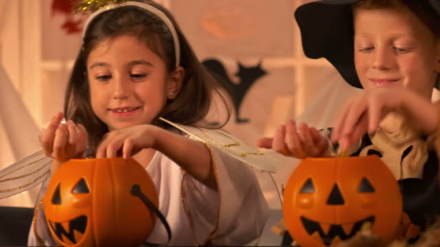 HD DOLLY: Children Counting Halloween Candies HD1080p: DOLLY shot of three adorable children taking candies out of Halloween pumpkins while sitting at table in workshop class. candy stock videos & royalty-free footage