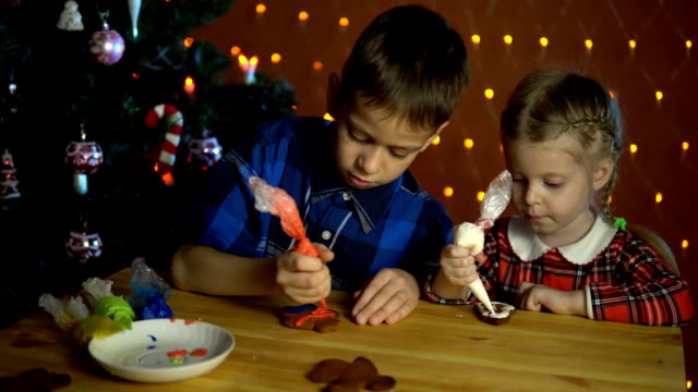 Children cover with a colorful glaze cakes, next to the Christmas tree. video
