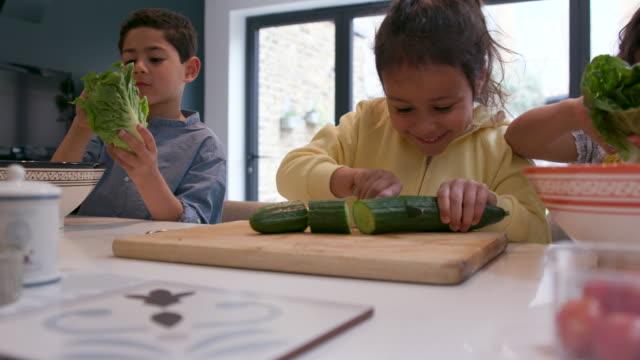 children cutting up vegetables for lunch - preparing food together - przygotowywać jedzenie filmów i materiałów b-roll