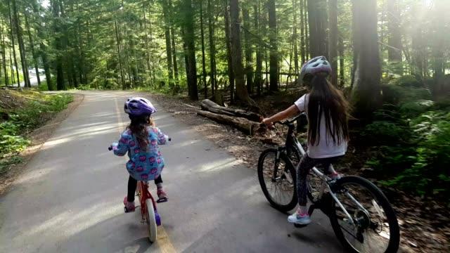 Children cycling through a lush green forest
