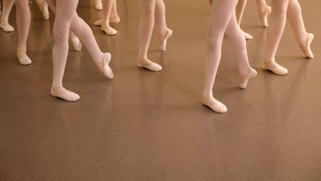kinder tanzen in einem ballettstudio, nahaufnahme der füße in pointe-schuhen. - ballettschuh stock-videos und b-roll-filmmaterial