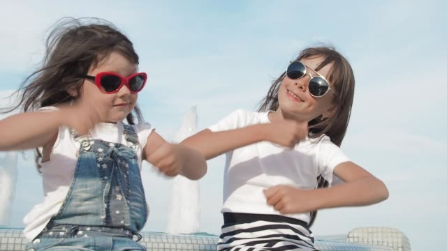 Children dancing in front of fountain. Children dancing in front of fountain. Happy girls at resort. Dancing on sunset. sister stock videos & royalty-free footage