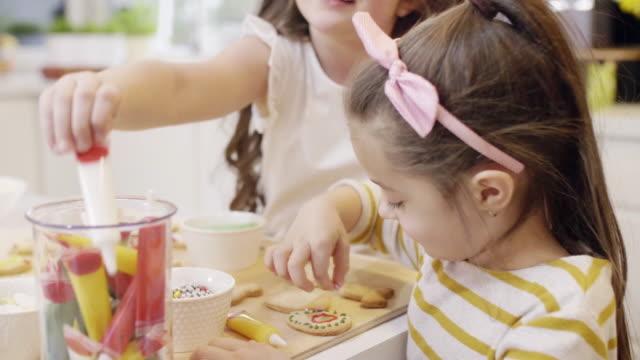 children decorating cookie at kitchen - посыпать стоковые видео и кадры b-roll