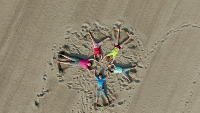 Children draw on the sand with their feet