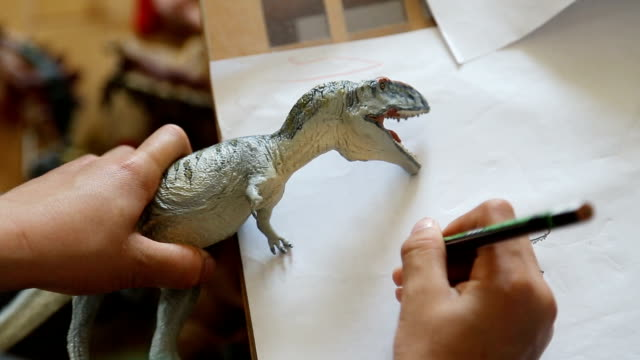 children drawings dinosaur, close up at hand hd. - dinosaur stock videos and b-roll footage