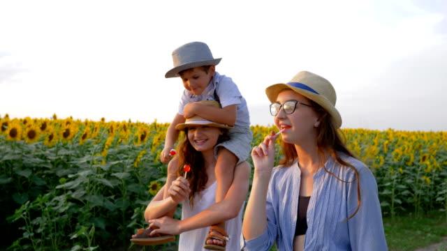孩子們喜歡在野外散步時用草帽在田野裡吃棒糖, 在戶外 - 波板糖 個影片檔及 b 捲影像