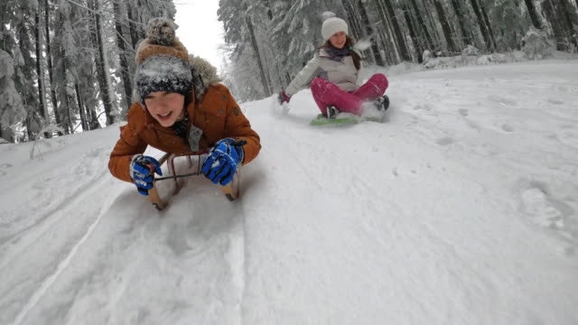 barn som njuter av spann i vinterskogen. - snow kids bildbanksvideor och videomaterial från bakom kulisserna
