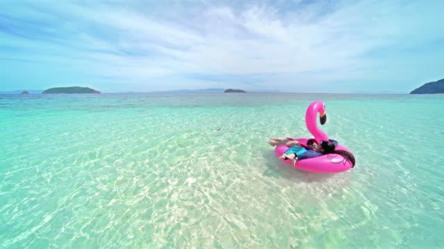 vídeos de stock, filmes e b-roll de criançamenina brincando no mar - inflável