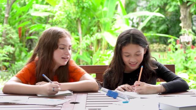vídeos de stock e filmes b-roll de children girls doing homework and drawing together in garden at home - girl study home laptop front