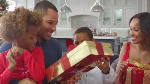 barn som ger jul klappar till föräldrar sköt på r3d - christmas gift family bildbanksvideor och videomaterial från bakom kulisserna