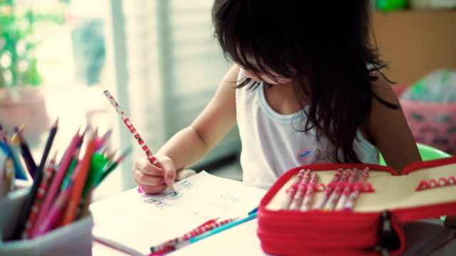 Children (6-7) hand writing at home. - video