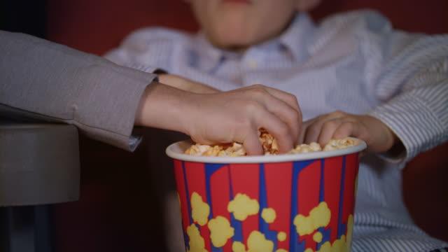 vídeos de stock, filmes e b-roll de mãos de crianças tirando pipoca de caixa de papel. comida de cinema para crianças - balde pipoca