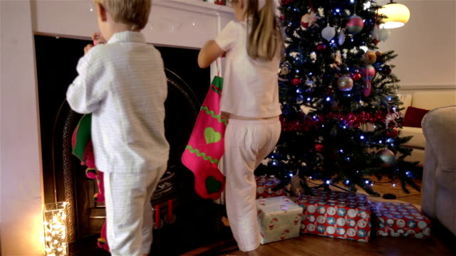 Children hanging stockings by the chimney video