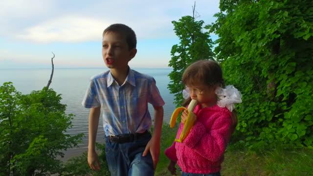 vídeos de stock e filmes b-roll de crianças ter um descanso na floresta sobre os bancos de um grande lago. menina criança ingere uma banana. rapaz adolescente diz a sua história. - margem do lago