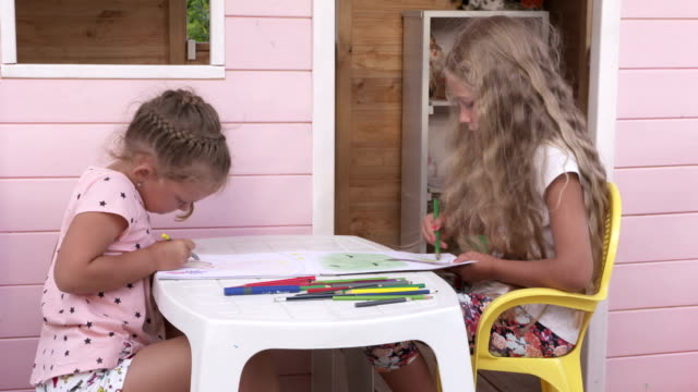 Children have fun together playing on the veranda of a wooden pink playhouse video