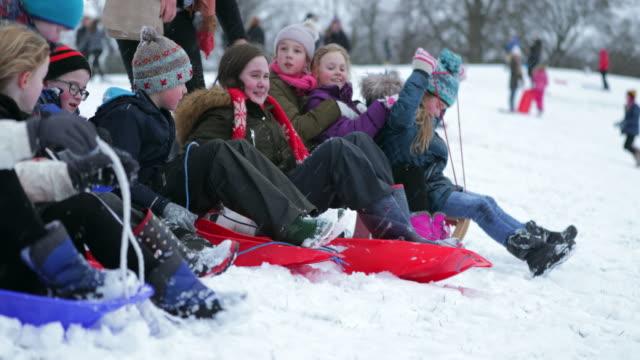 children having a sled race - sci sci e snowboard video stock e b–roll