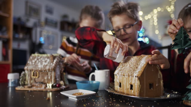 vídeos de stock e filmes b-roll de children having fun decorating gingerbread houses - christmas cookies