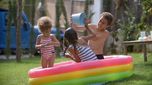 vídeos y material grabado en eventos de stock de niños divirtiéndose en la piscina infantil - backyard pool