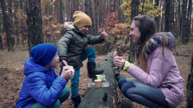 Children having snack in the forest during walk