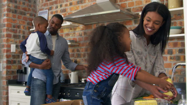 children helping parents to prepare meal in kitchen - family home video stock e b–roll