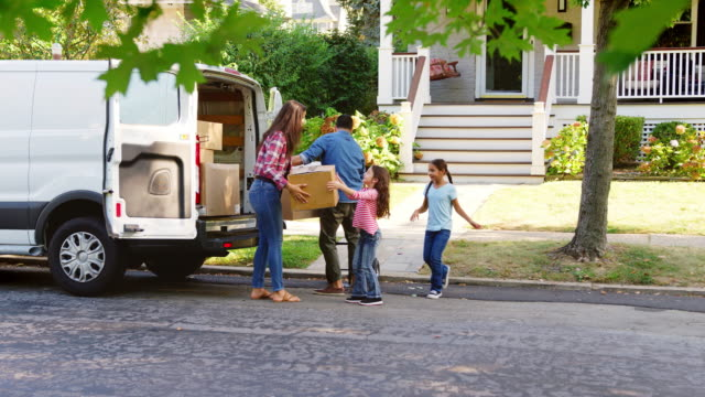children helping unload boxes from van on family moving in day - new home stock videos & royalty-free footage