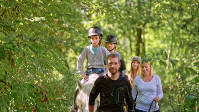 vídeos de stock, filmes e b-roll de cavalgadas de crianças na floresta - cavalgar