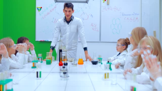 Children in chemistry class. Teacher and children in chemistry class video
