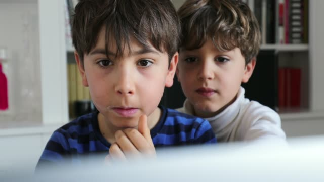 children in front of computer screen in the morning. authentic candid kids surfing the internet looking for media online - solo un bambino maschio video stock e b–roll