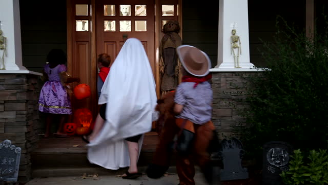children in halloween costumes trick or treating - halloween 個影片檔及 b 捲影像