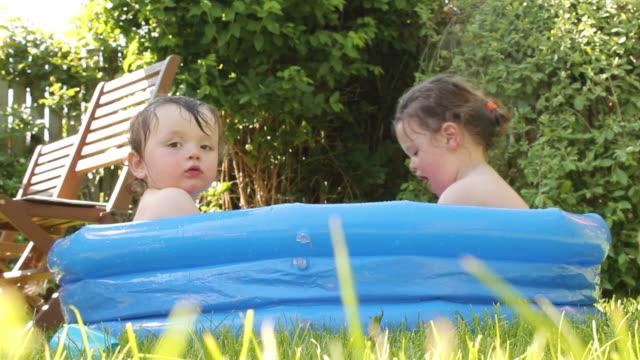 vídeos de stock, filmes e b-roll de remar crianças na piscina em um dia ensolarado - inflável
