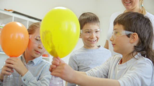 Children in the classroom smiling because they made their balloons inflate during a science experiment