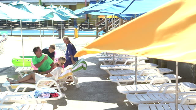 Children join parents relaxing on pool deck video