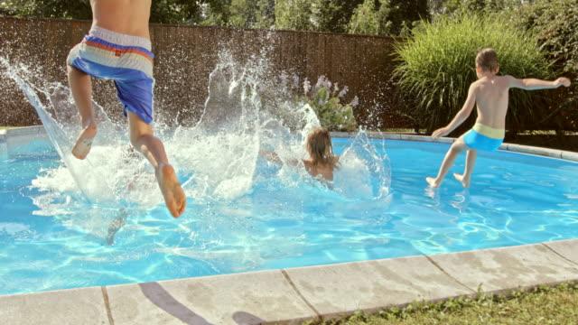 vídeos y material grabado en eventos de stock de cámara lenta cs niños sumergiéndose en la piscina para tomar el sol - backyard pool