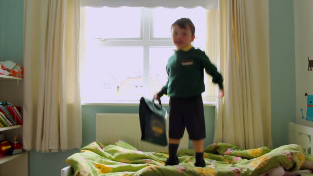Children jumping on bed with school uniform getting ready for first day back at school video