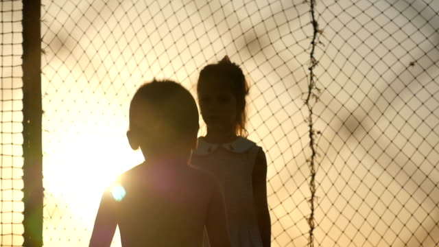 children jumping on the trampoline at sunset cute boy and girl jumping on the trampoline in the sunset action movie stock videos & royalty-free footage